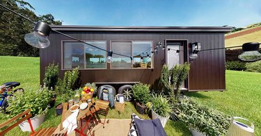 exterior of ikea tiny home project featuring greenery