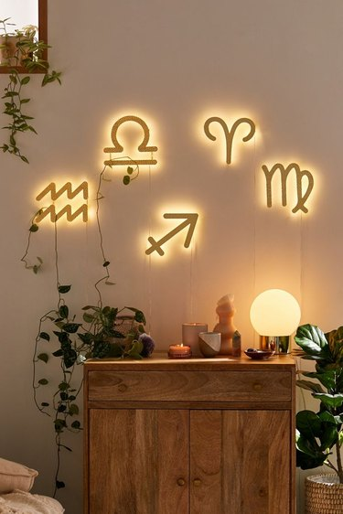 Zodiac sign LED lights on wall with wood cabinet below