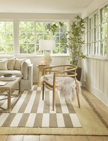 living room space with striped rug and wood chair