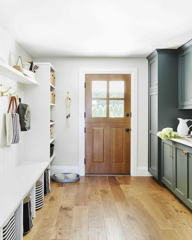 forest green and white mudroom storage with pine floors