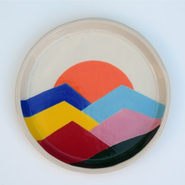Plate with different colored mountains with the sunset.