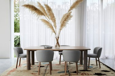 eco-friendly furniture with modern dining room with wood table, gray chairs, and large pampas grass centerpiece