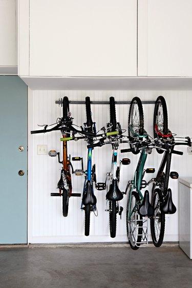 Bike storage using a rack in the garage next to blue door