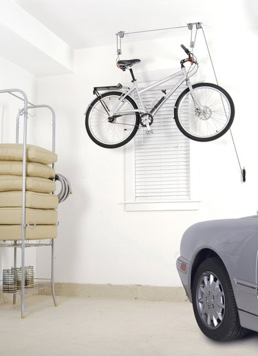 bike storage hanging from a pulley system in a garage with a car