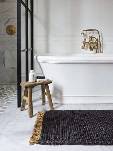 black rug in front of tub