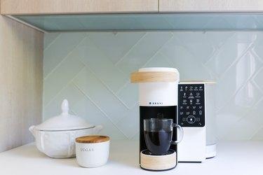 bruvi coffee system in front of light blue backsplash next to sugar bowl