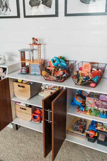 Playroom Organization Ideas with toys in baskets stored in buffet