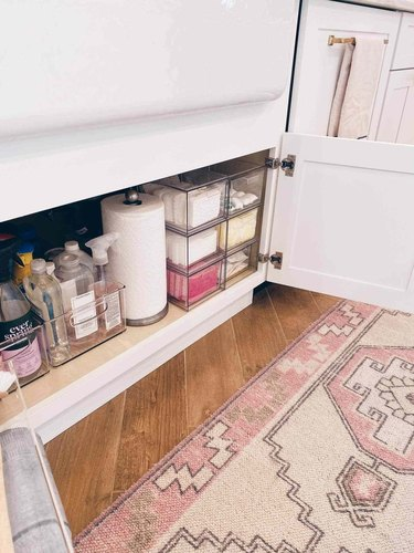 under sink storage in narrow area with clear bins and paper towel roll
