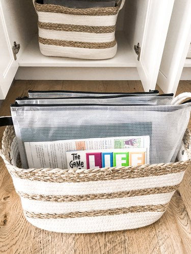 board game storage in zipped pouches in a basket