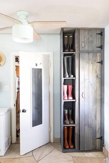 boots shelved in a standing cabinet in a laundry room