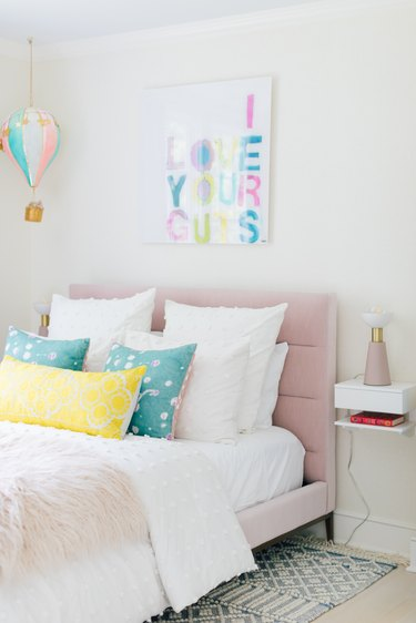 Kids' room organization with small bedside shelf and with colorful decor