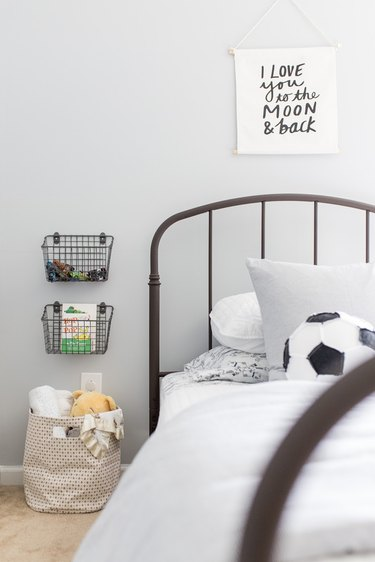 Kids' room organization with wire wall baskets and metal bed frame