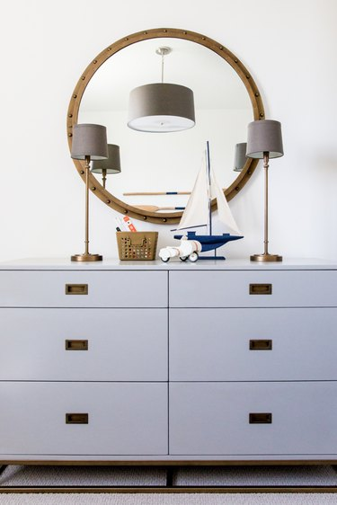 Kids' room organization with gray dresser and round mirror