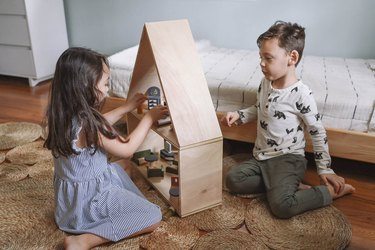 Little girl and boy playing with dollhouse