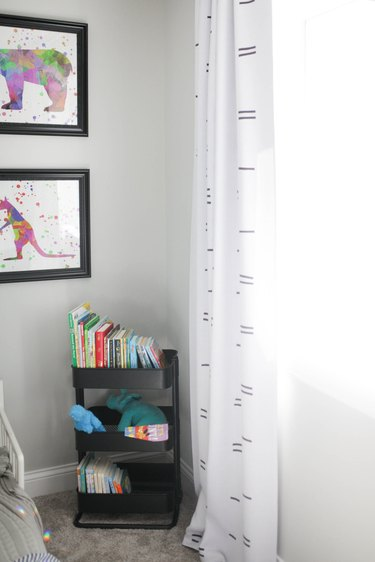 Kids' room organization with black bar cart as bookshelf with books