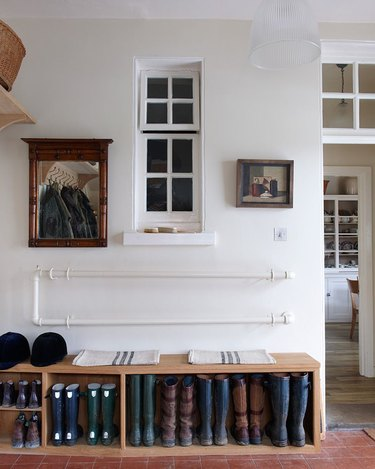 white hallway with bench and boots storage underneath