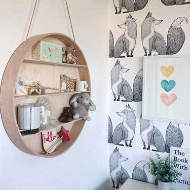 Kids' room organization with circular hanging shelf and black and white fox wallpaper