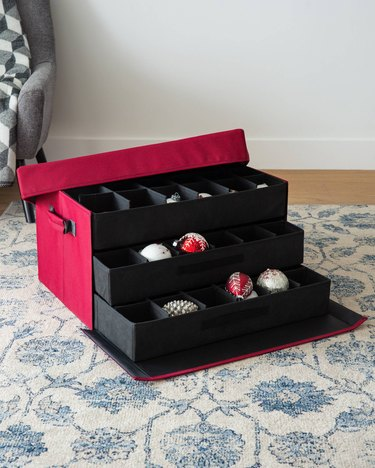 Red ornament storage container with three removable trays