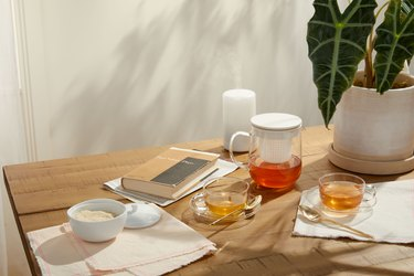table with notebooks, plant, and tea accessories