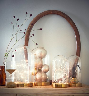 shelf with glass domes, lights, and dry greenery