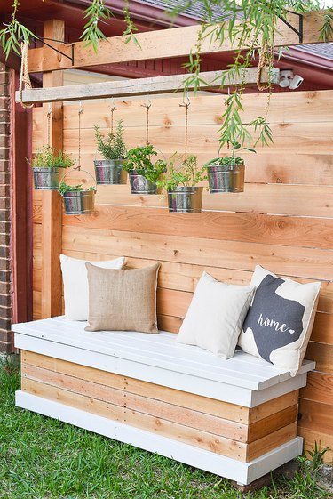 DIY storage bench for backyard in white and a wood finish with throw pillows