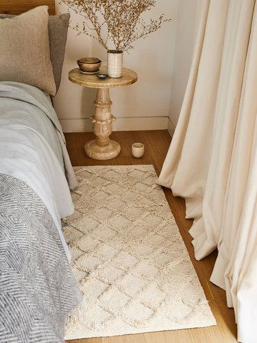 textured rug next to bed