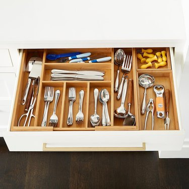 Bamboo utensil drawer organizer with assorted cutlery and tools