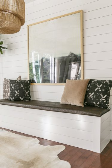 DIY storage bench with white shiplap and mud cloth pillows