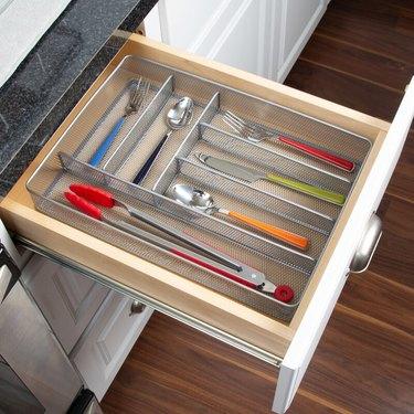 Steel utensil drawer organizer with colorful utensils in white drawer
