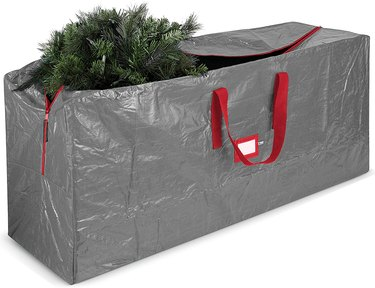 Gray Christmas tree storage bag with red handles and label