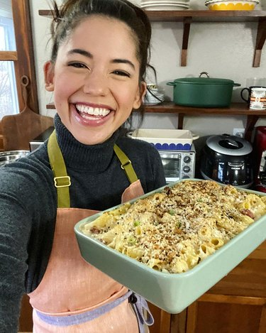 Molly Yeh of my name is yeh holding everything bagel mac and cheese