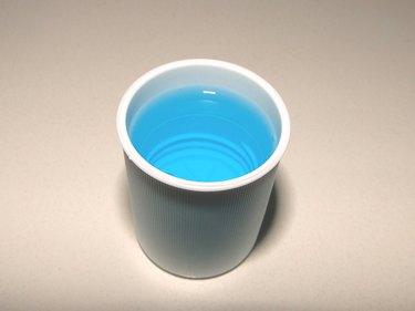 blue mouthwash in mouthwash bottle cap on white surface