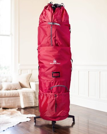 Red rolling Christmas tree storage bag in living room