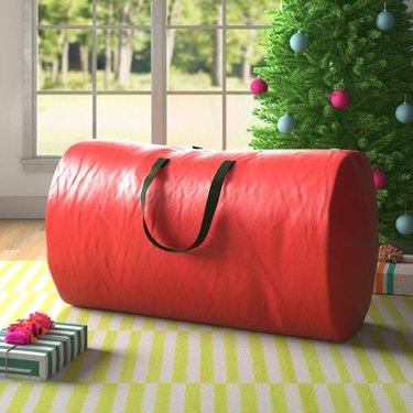 Red Christmas tree storage bag with black handles on rug next to Christmas tree