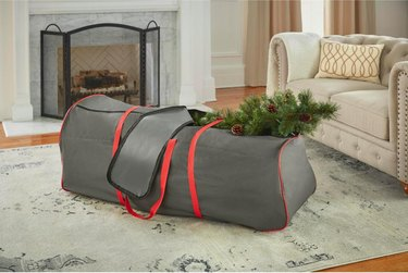 Gray and red Christmas tree storage bag with Christmas tree in living room