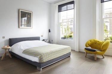 The master bedroom features oak floors and a whimsical Finn Juhl Pelican armchair.