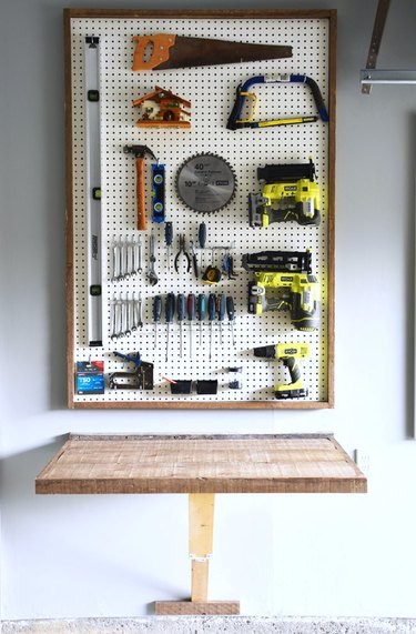 DIY garage organization idea with pegboard with power tools above a work bench
