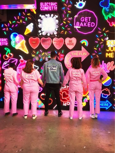 Electric Confetti team in front on neon art–filled wall