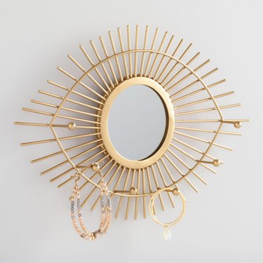 Earring Storage with Brass eye shaped mirror with jewelry hooks.