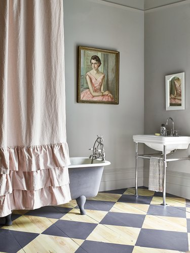 gray bathroom with checkered floors and clawfoot tub covered with a pink shower curtain