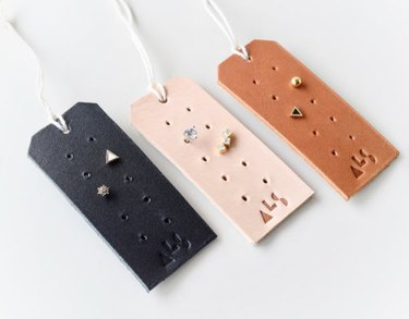 Earring Storage with Black, pink and brown leather tags with stud earrings.