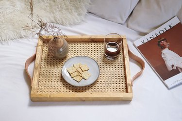 DIY cane webbing tray on bed with wine, crackers and magazine