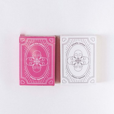 Actually Curious pink and white card game boxes