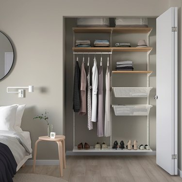 Bedroom with closet organizer unit, clothes, shoes, nightstand.