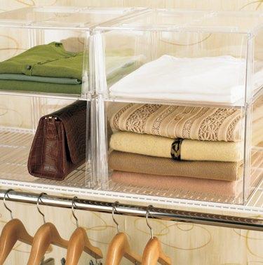 Closet Organizer with Clear plastic storage bins, sweaters, purse.