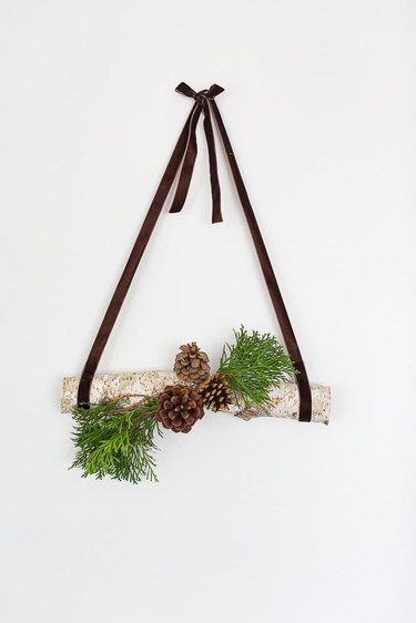 hanging log decor with pine cones and grass