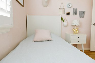 Kid's Room Organization Guide in pink girls room with white nightstand