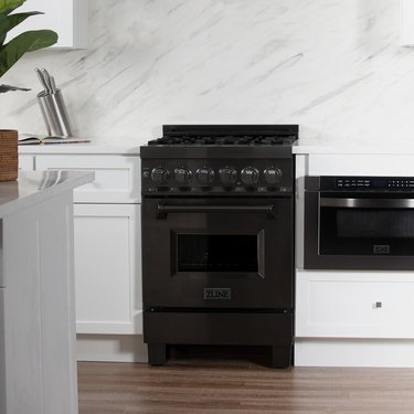 Black gas range in white kitchen. Small Stove and Oven