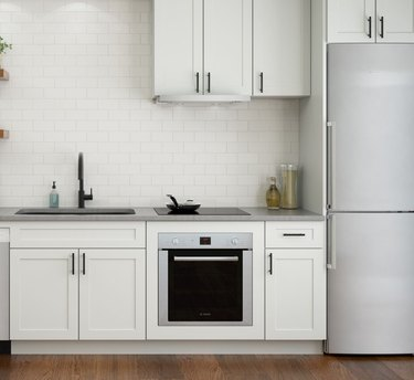 Induction cooktop with wall oven in white kitchen. Small Stove and Oven