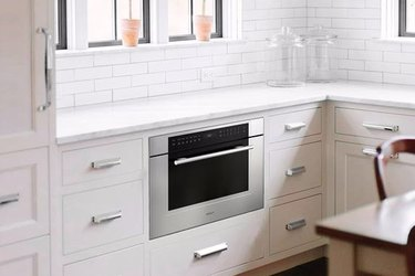 Wall oven under counter in white kitchen. Small Stove and Oven
